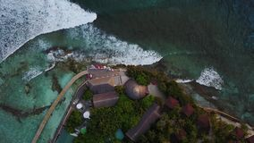 Top view of Maldives island, cameragoes down to the bar at luxury tropical hotel resort. Drone descending over the stock video