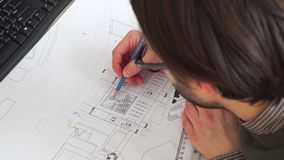 Top view of male design engineer sits at the desk, blueprints laying on her desk