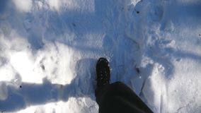 Top view on male feet walking on snowy trail. Guy in boots going on road stepping on white clear snow. Unrecognizable. Hiker strolling through forest. Winter stock video