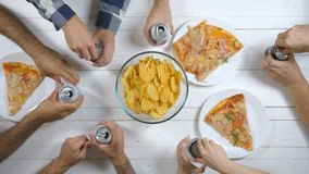 Top view male and female hands opening and clicking aluminum cans with soda on wooden table background. Group of best. Friends sitting at the desk and toasting stock footage