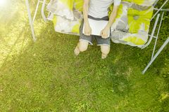Top view of male freelancer sitting on the swing couch on summer holiday resort on grass. Top view of male freelancer sitting on the swing couch on a summer Stock Image