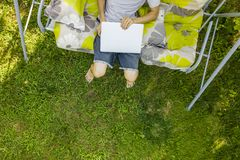Top view of male freelancer sitting on the swing couch on summer holiday resort on grass. Top view of male freelancer sitting on the swing couch on a summer Stock Photography