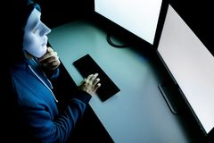 Top view of male hacker in mask under hood using computer to hack into system and trying to commit computer crime. Top view of male hacker in mask under hood stock photo