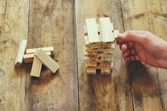 Top view of male hand placing wooden block on a tower. planing and strategy concept.  stock images