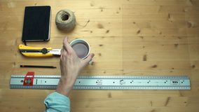 Top view male hand placing working supplies at wooden desk. Metal ruler, cup of tea, notepad, craft rope at desk stock video footage