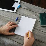 Top view Male hand writes in notebook. Home workplace. Top view male hand writes in a notebook close up. Home workplace Royalty Free Stock Photos