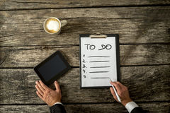 Top view of male hand writing a To do list on a white sheet of p. Aper with digital tablet and cup of coffee alongside on his textured rustic wooden desk Stock Image
