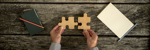 Top view of male hands assembling two wooden puzzle. Pieces with notebook and notepad, pen and pencil lying on textured wooden desk, panoramic image Stock Images