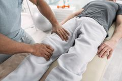 Top view of male hands doing a massage. Professional treatment. Top view of male hands doing a medical massage for the patient Royalty Free Stock Image
