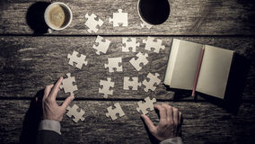 Top view of male hands rearranging puzzle pieces trying to find Stock Photography