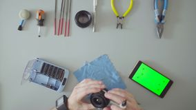 Male hands repair lens on grey table. Top view. Male hands scrolling a smartphone with green screen. Male hands repair photo lens on grey table stock video footage