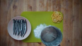 The process of cooking a small fish, preparing for frying in oil in a frying pan. Top view of a male hands sprinkling flour through a sieve onto a green chopping stock video footage