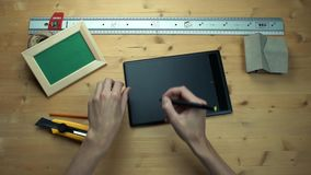 Top view male hands using digital graphic tablet at wooden desk. Metal ruler, house model, craft rope, realistic mockup wooden photo frame, yellow paper knife stock video
