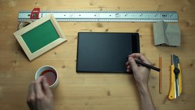 Top view male hands using digital graphic tablet at wooden desk. Metal ruler, house model, cup of tea, realistic mockup wooden photo frame, yellow paper knife stock video