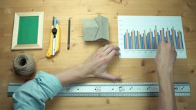 Top view male hands using digital graphic tablet at wooden desk. Top view male hands working with printed graphs making notes with marker at wooden desk. Metal stock video footage