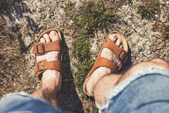 Top view of male legs in brown leather sandals and blue jean shorts. Standing on a rocky trail Royalty Free Stock Image