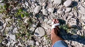 Top view of male legs going on the stones next to the river. Closeup top point of view of male legs walking on stony. Beach toward river. Camera motion. Man is stock footage
