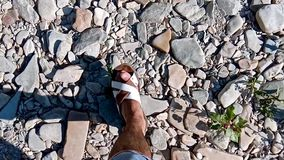 Top view of male legs going on the stones next to the river. Closeup top point of view of male legs walking on stony. Beach toward river. Camera motion. Man is stock video footage