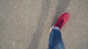 Top view of men`s legs in red sneakers walking on asphalt stock footage