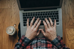 Top view of man hands in red checkered shirt using laptop and dr Stock Photography