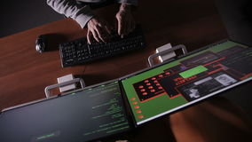 TOP VIEW. Man hands typing on a keyboard in a dark room. Hacker, it professional, computer specialist at work stock footage