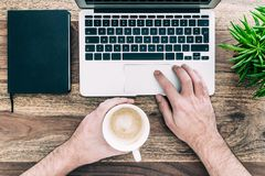 Man holding cup of coffee while working on laptop computer royalty free stock images