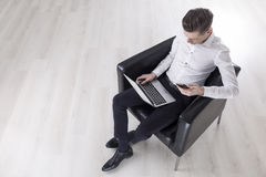 Top view of man with laptop in armchair Royalty Free Stock Photo