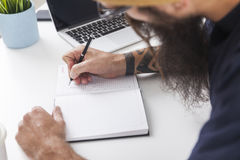 Top view of man with long beard taking notes Royalty Free Stock Photography