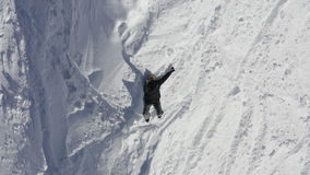 Top view man lying on snow and showing shaka sign by hand for greeting. Drone flying over happy man lying on snow at winter mountain. Aerial view tourist on stock footage