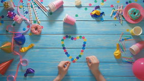 Top view man makes a heart shape using confetti. Stock footage Top view man makes a heart shape using confetti stock video footage