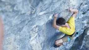 Top view of man rock climber, climbing sport route on a cliff, searching, reaching and gripping holds. outdoors rock
