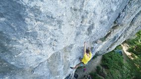 Top view of man rock climber in yellow t-shirt, climbs on a cliff, searching, reaching and gripping hold. outdoors rock