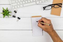 Top view of a man`s hand writing on check list paper. On white wooden table background stock photography