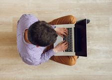 Top view of man sitting on the floor and working with a laptop Royalty Free Stock Photos