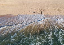Aerial view of the ocean waves washing on the beach. Top view of man standing on the beach while the ocean wave crushing the coast stock photos