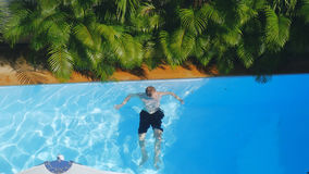 Top of view of man swimming in outdoor pool stock photos