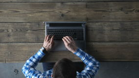 Top view of man typing on laptop. Top view of a young man typing on laptop computer at rustic wooden table stock footage