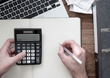 Top view of man using calculator on desk with folder, receipts or bills and laptop stock photography
