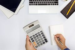 Top view. Man using calculator and writing make note. stock images