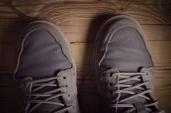 Top view of a man wearing a pair of sneakers. Shoes standing on a wooden floor Royalty Free Stock Images