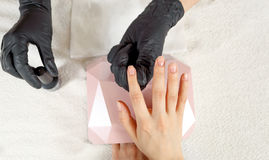 Top view manicurist holds customer hands. Fingernails are covered with clear nail polish Stock Image