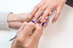 Top view manicurist removing cuticle from the nail Royalty Free Stock Photos