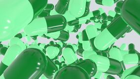 Top view of many capsule pills green capsule drop from the top in different position. Drugs for treatment medication.