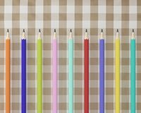 Top view of many colorful Pencils pencils on fabric tartan plaid. Pattern background. minimal idea concept. flat lay. concept for education Royalty Free Stock Image