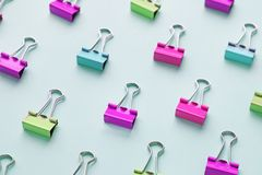 Top view of many multicolor binders clips on pastel blue background. stock image