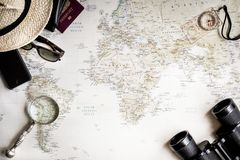 Top view of a map of the world for planning a trip. With a pair of binoculars, compass, magnifying glass, coffee, phone, and more Royalty Free Stock Photography