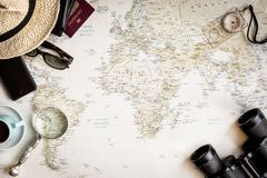 Top view of a map of the world for planning a trip. With a pair of binoculars, compass, magnifying glass, coffee, phone, and more Royalty Free Stock Photo