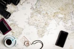 Top view of a map of the world for travel plans with a vintage look. A selection of random travel items to accompany royalty free stock photos
