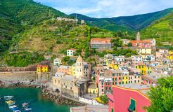 Top view of marina harbor with boats, Chiesa di Santa Margherita church, green hills and typical colorful buildings houses in Vern. Azza village, National park stock image