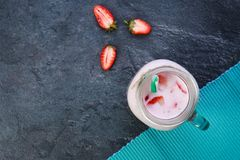 A top view on a mason jar with jogurt on a marble background. Food concept. A top view on a mason jar with tasty fresh jogurt and three pieces of strawberries stock image